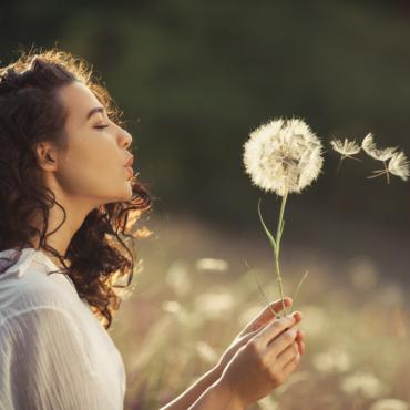 mujer soplando un dandelion